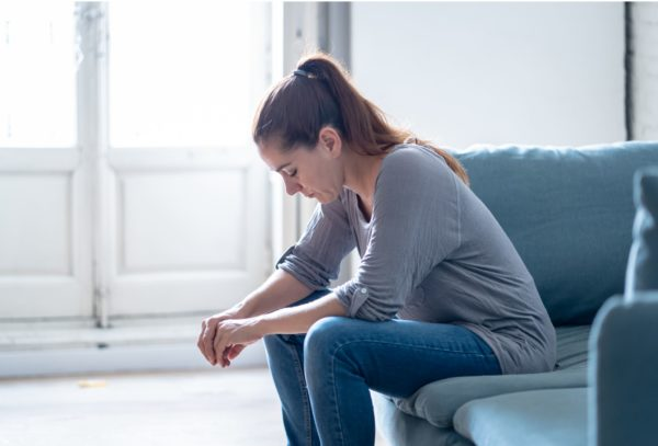 A young woman sits hunched over on a couch with her head down