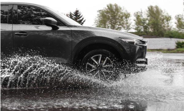 An SUV drives through water on a street