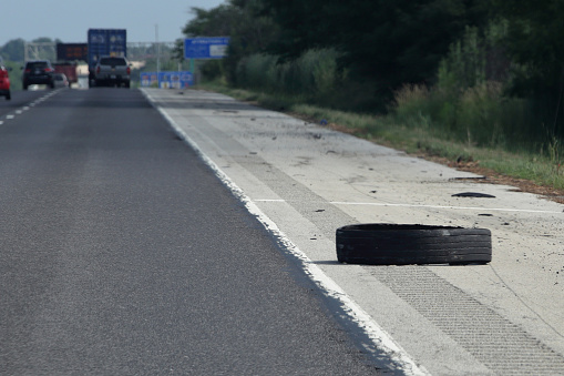 A piece of tire comes off a semi and lies on the shoulder of a highway