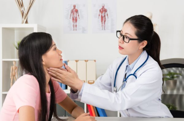 A doctor examines a patient for a neck injury