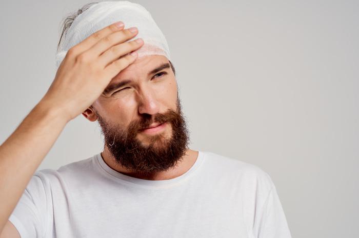 bearded man with bandaged head