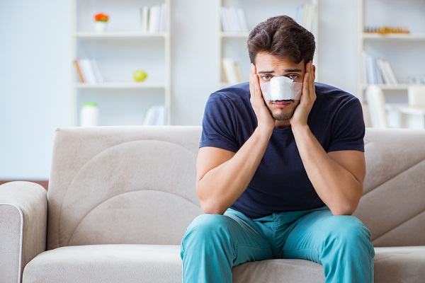 Young man recovering at home after plastic surgery nose