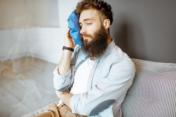 Bearded man with headache applying ice bag while sitting on the couch at home