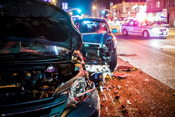 A nighttime crash scene with two heavily damaged cars and a police cruiser blocking traffic in the background.