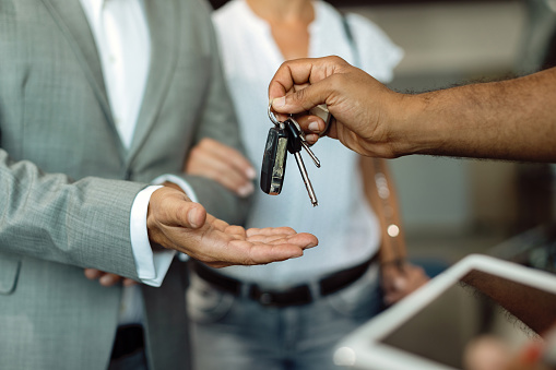 Close-up of businessman receiving car keys from a mechanic at auto repair shop.