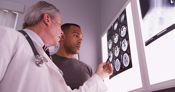Medical doctor reviewing brain image scans with a patient.